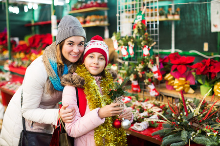 Girl with young mother choosing floral decoration for Xmas. Focus on woman