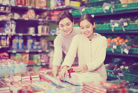 happy woman with daughter choosing delicious cookies in supermarket Фото со стока