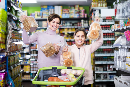 cheerful woman with daughter choosing delicious bread in supermarket