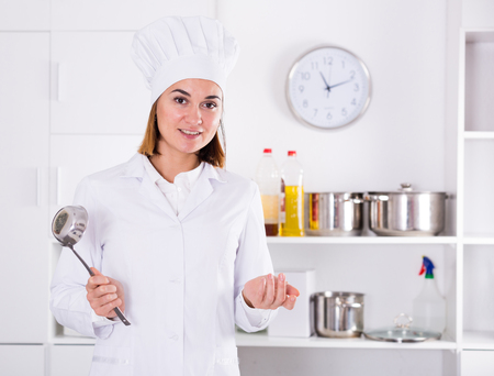 Smiling woman cook making tasty dishes in kitchen