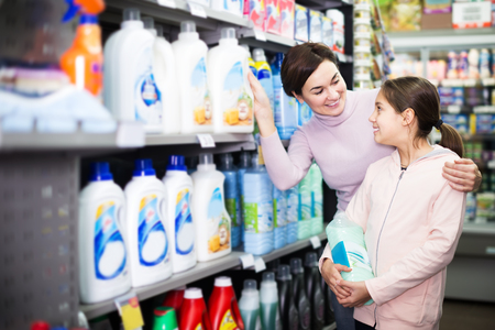 Young female customer with teenage daughter searching for cleaners in supermarket Reklamní fotografie