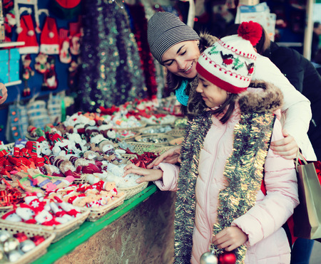 Positive woman with small daughter in Christmas market