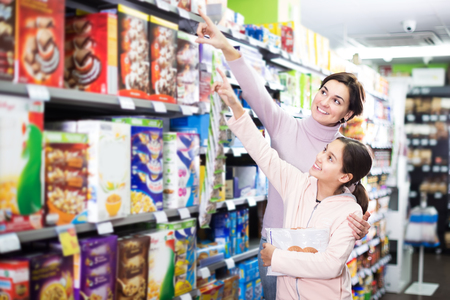 Young female shopper with teenage daughter searching for breakfast cereal in supermarket
