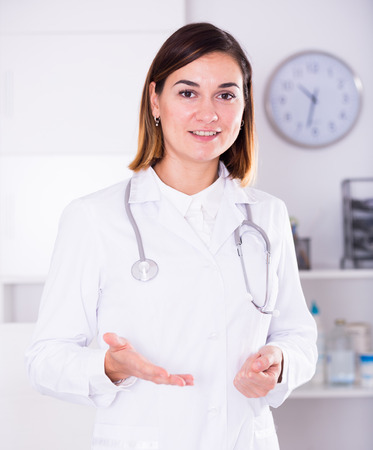 Smiling woman doctor working effectively in her office Imagens