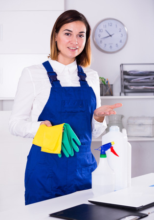 Young female cleaner working productively on task in office