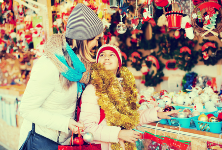 Ordinary mother with small daughter in Christmas market Stock Photo