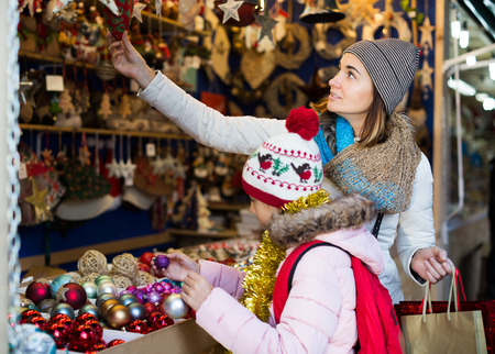 Portrait of girl with glad mom buying decorations for Xmas. Focus on girl