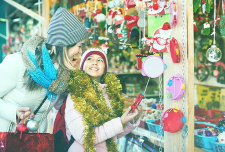 Beautiful smiling female customers staring at counter of Christmas market. Focus on woman Stock Photo