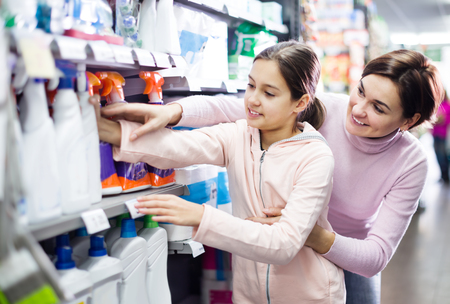 Young woman customer with girl looking for cleaners for a home at supermarket. Focus on both persons Reklamní fotografie