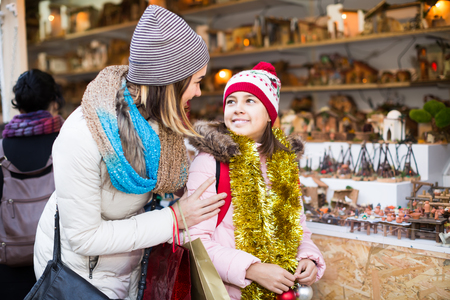 Little girl with cheerful mom buying figures and workpiece for creating Christmas scenes at an open air market
