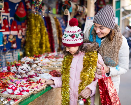 Happy mother with glad little daughter buying decorations for Xmas at an open air market 스톡 콘텐츠