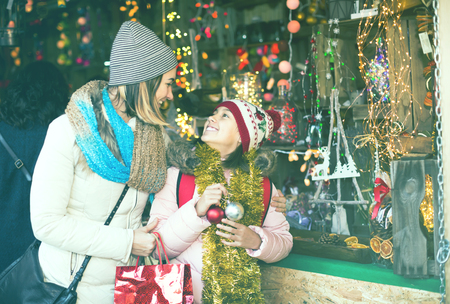 vigorous mother with little daughter buying decorations for Xmas at an open air market 스톡 콘텐츠