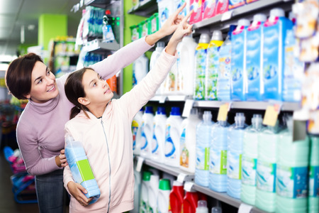 Young female client with teenage daughter searching for cleaners in shop. Focus on girl Reklamní fotografie