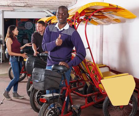 Conductor de bicitaxi hombre afroamericano positivo de pie cerca del ciclo del rickshaw