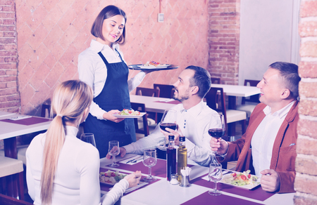 Friendly  female waiter bringing order to visitors in country restaurant