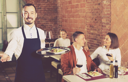 Nice male waiter showing country restaurant to visitors