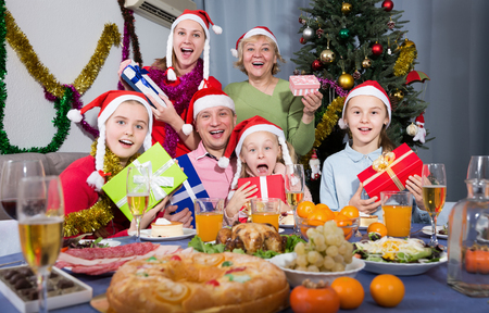 Positive family sitting with gifts at celebrating Christmas at dinner