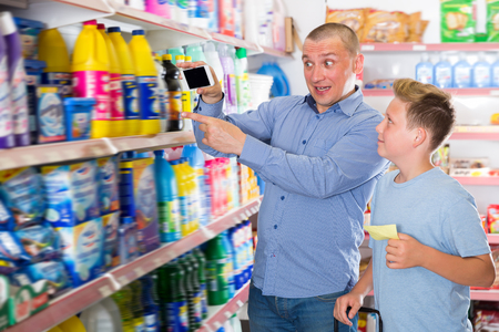 Glad man with boy consulted about purchasing in store