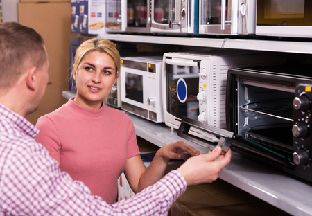 couple choosing new microwave for kitchen in furniture store Imagens