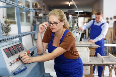 Vitrier féminin confiant travaillant sur la machine à chanfreiner en ligne droite de verre dans l'atelier Banque d'images