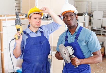 Confident male contractors working with handheld power tools in overhauls indoors