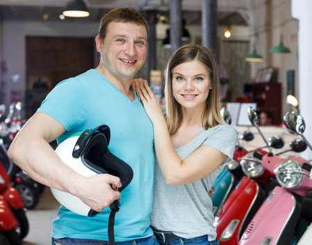 Portrait couple who is satisfied of shopping in moto store.