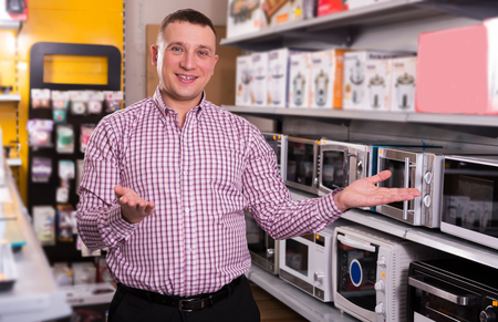 Middle-class  man choosing new microwave   in appliances store