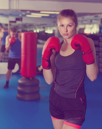 Portrait of positive woman who is training in box gym.