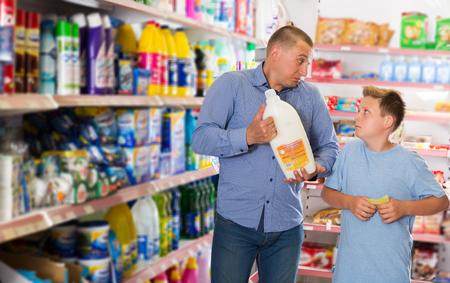 serious young man doing shopping with preteen boy looking at shopping list while choosing household detergents in store