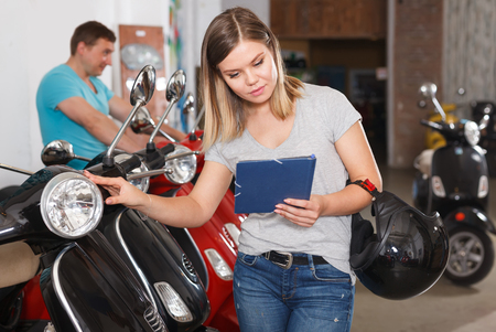 Young female reads a description of a motobike in the moto store.