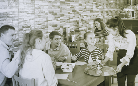 active brunette waitress serving cheerful family in comfy family cafe