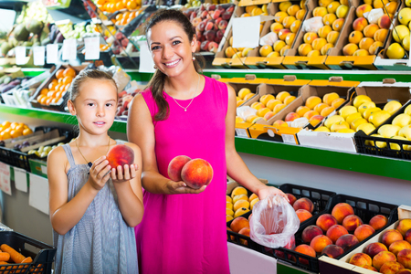 Young woman with little daughter picking peaches in fruit section in supermarket