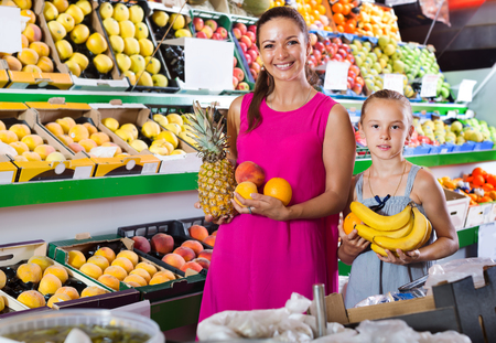 Positive mother with girl picking a different fruits in the supermarket. Focus on woman