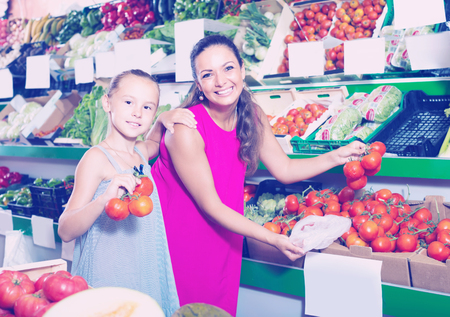 happy smiling young woman with daughter buying tomatoes in food store