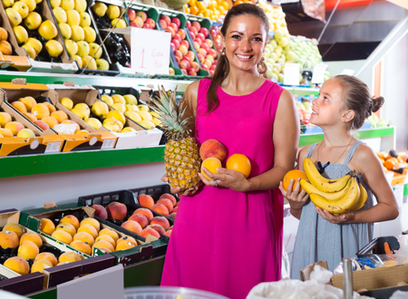 portrait of american young woman with female child buying variety of fruits on market