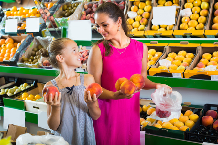 portrait of smiling  young mother with girl taking peaches on fruit market