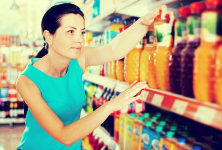 Atractiva mujer joven eligiendo jugo de frutas en la estantería del supermercado