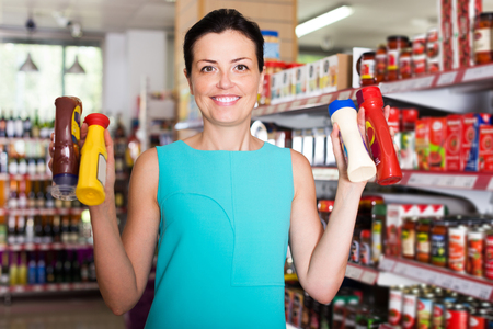 Happy woman choosing different sauces at the modern supermarket