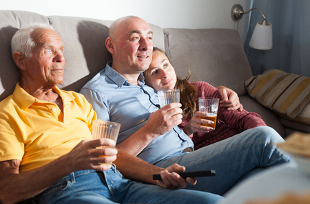 Family watching tv and drinking beer at home Stock Photo