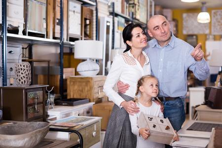 Familia positiva con niña eligiendo muebles para casa en showroom