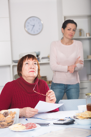 Sad young woman and mother with financial documents, quarrel at home interior