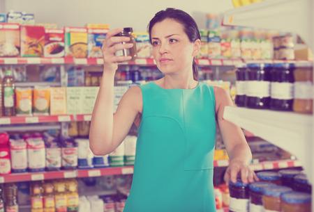 Smiling woman choosing the jar of fruit jam at modern supermarket Banque d'images - 124370730