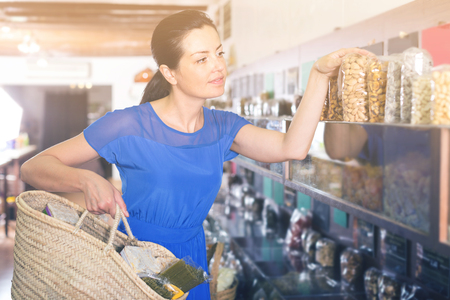Smiling woman is choosing sweet dry fruits in organic shop. 스톡 콘텐츠