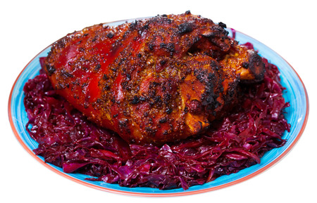Delicious oven baked pork knuckle with side dish of braised red cabbage and onion. Isolated over white background