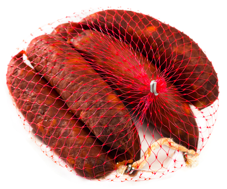 Spanish dry cured sausages chorizo in nylon packaging net. Isolated over white background