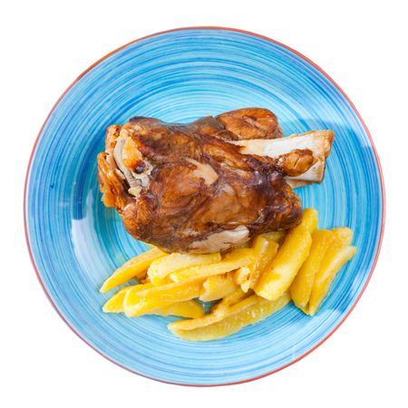Close up of delicious baked pork knuckle with potatoes, served  on  plate. Isolated over white background
