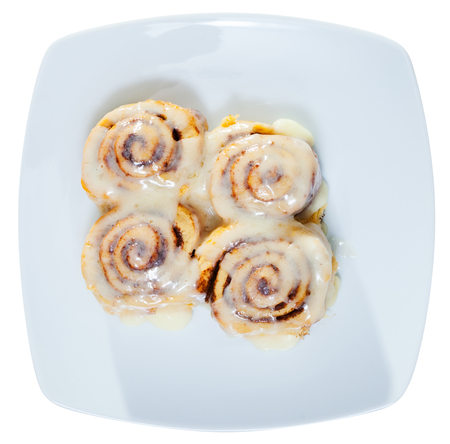 Top view of soft and fluffy cinnamon rolls topped with sugar glaze on white plate. Isolated over white background
