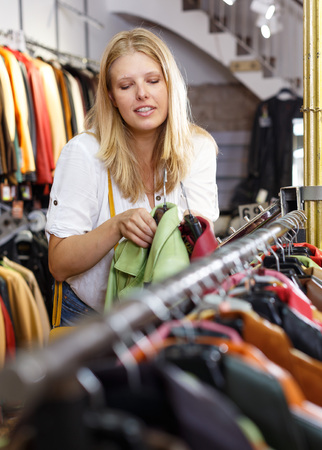 Attractive young woman choosing stylish leather jacket in clothing store