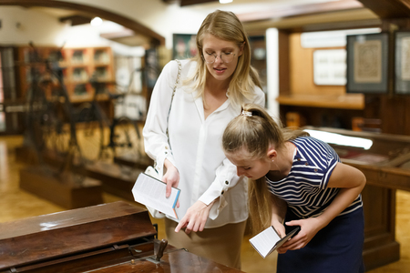 Young woman visitor with daughter with guide book pointing exhibition in museum of art
