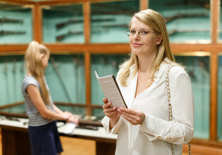 Portrait of woman holding guidebook in museum of art, girl on background